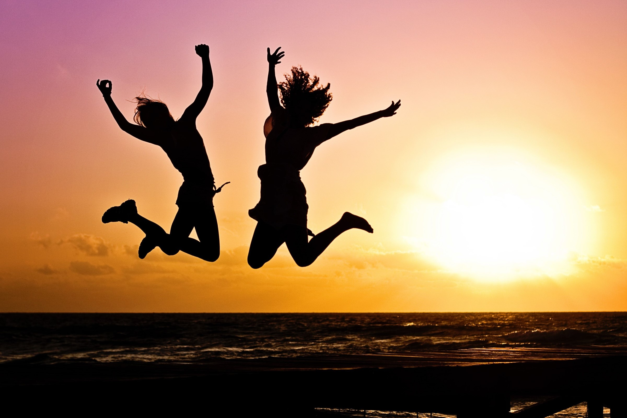 Silhouettes jumping on a beach