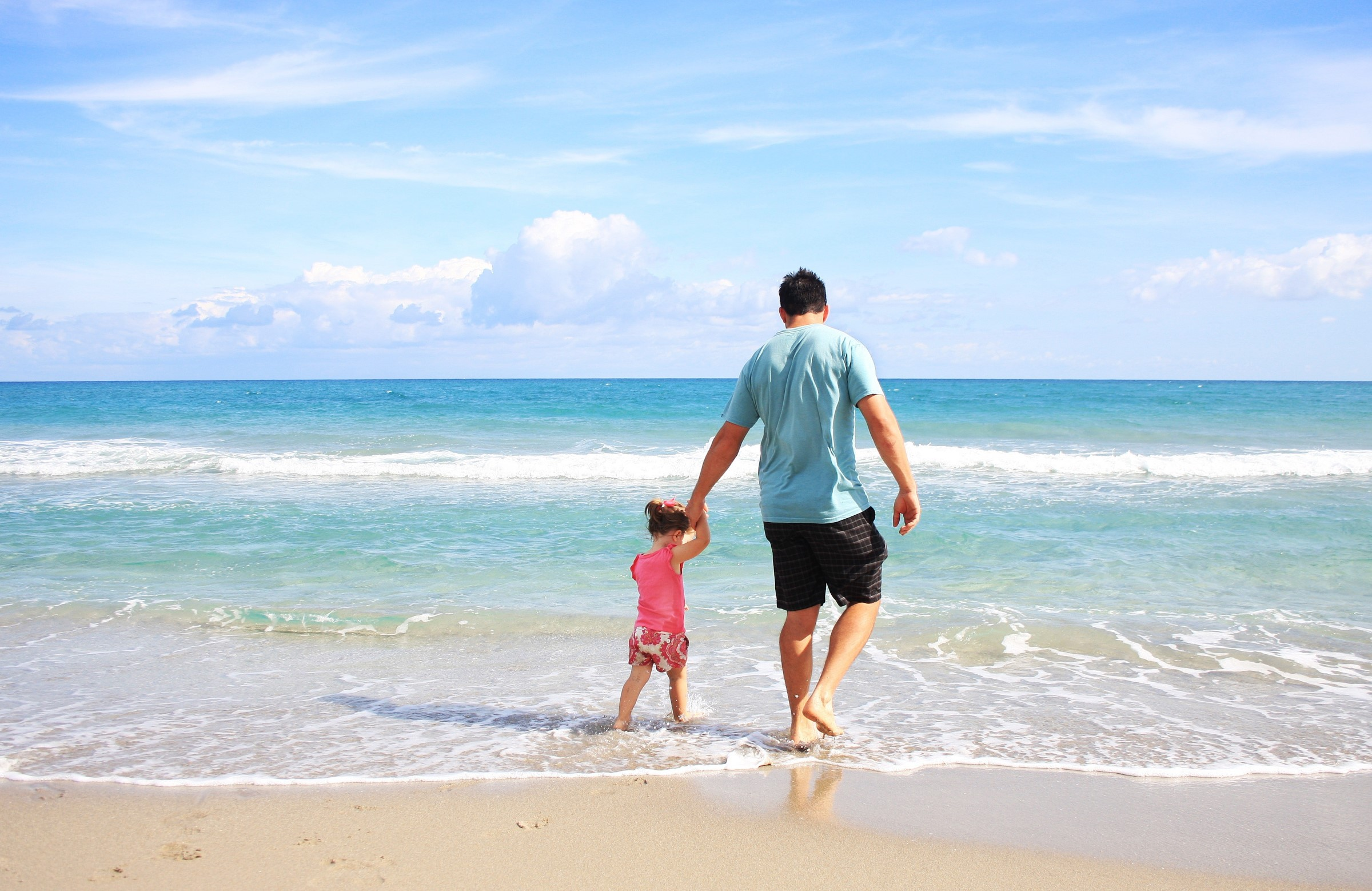 Father and daughter walking along a beach
