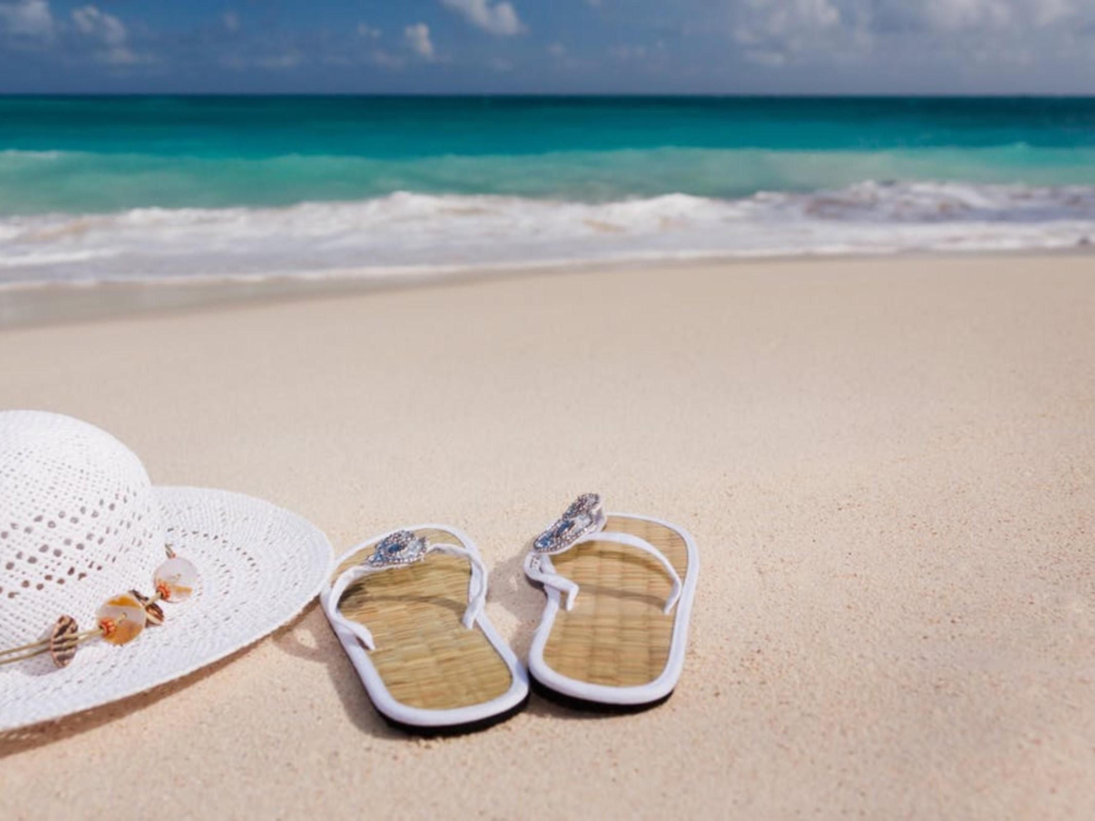 Sandals and sun hat on a sandy beach