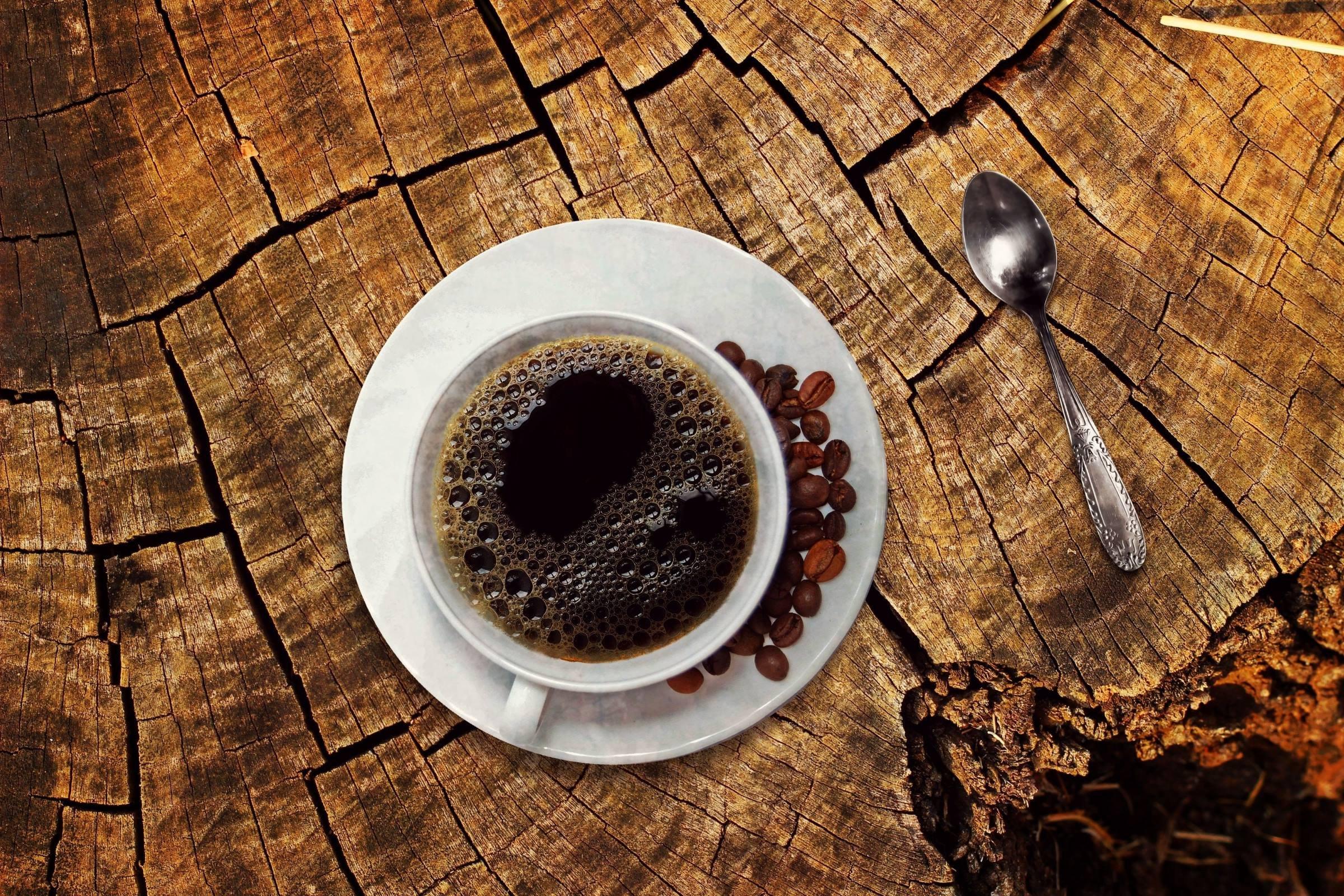 Cup of black coffee on tree stump