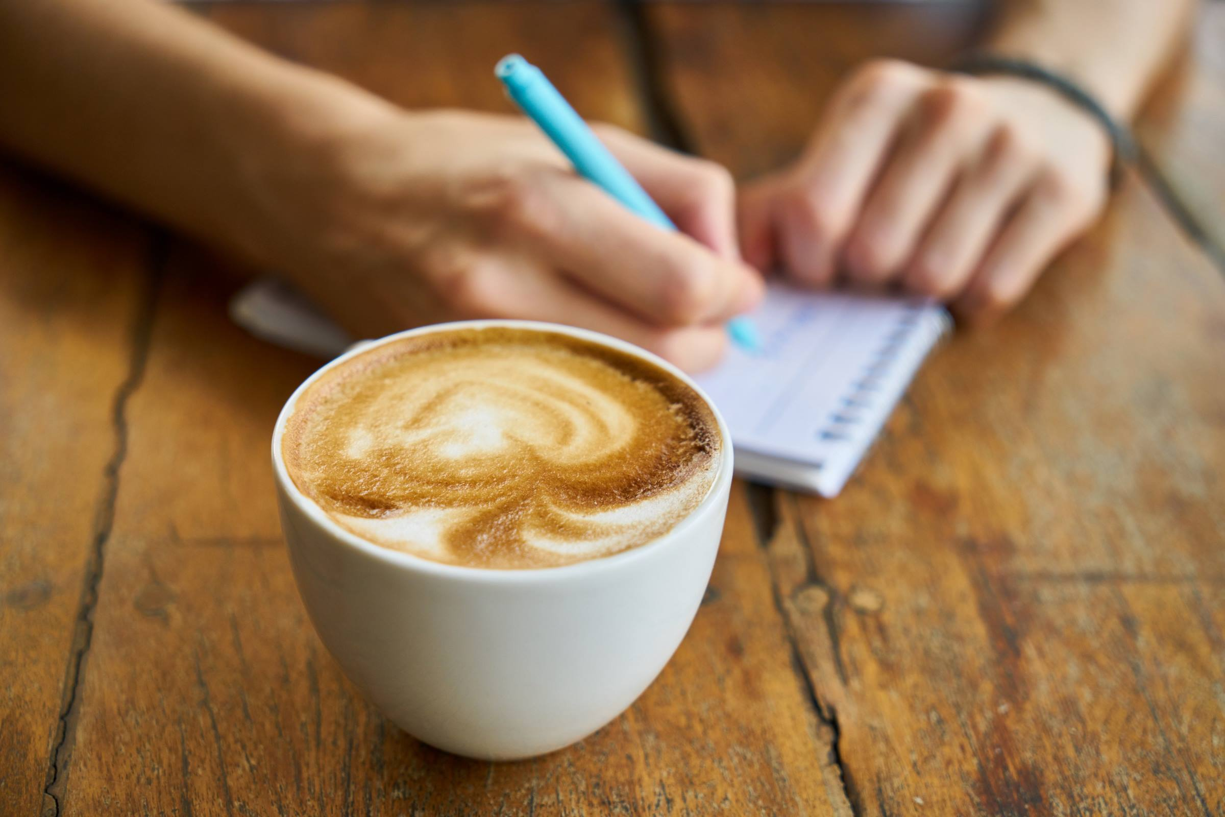 Cappuccino coffee with person writing