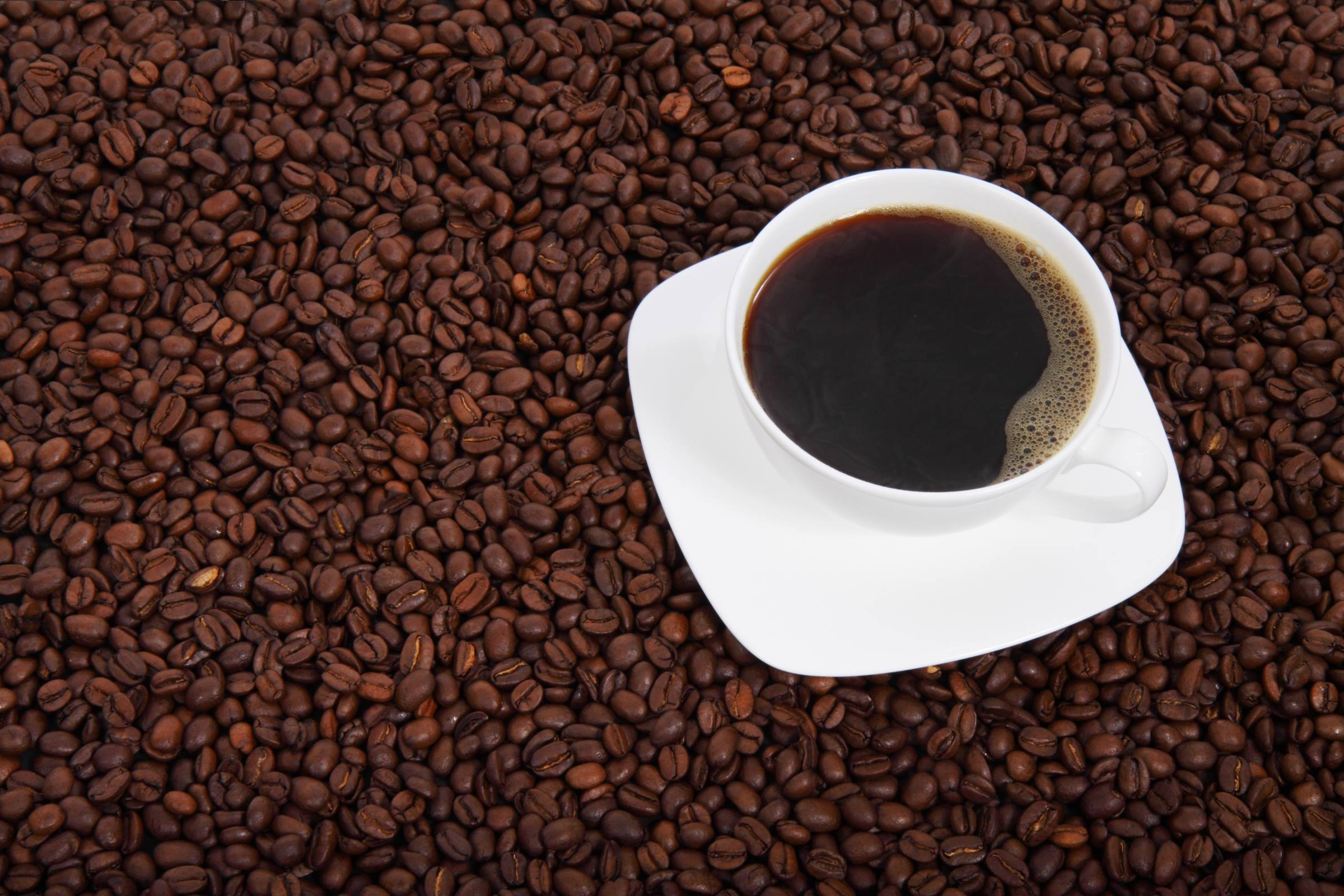 Cup of black coffee on coffee beans