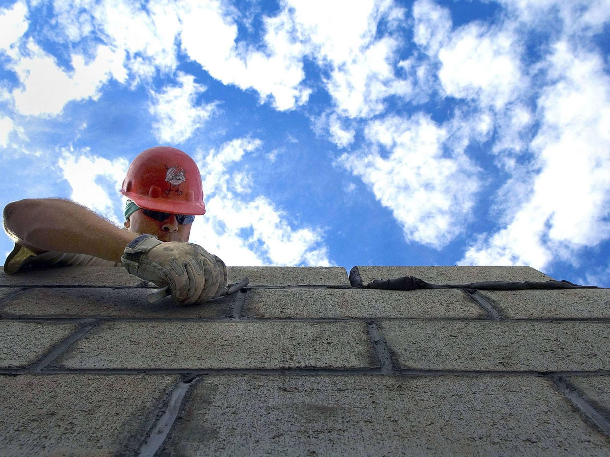 Worker roofer shingles