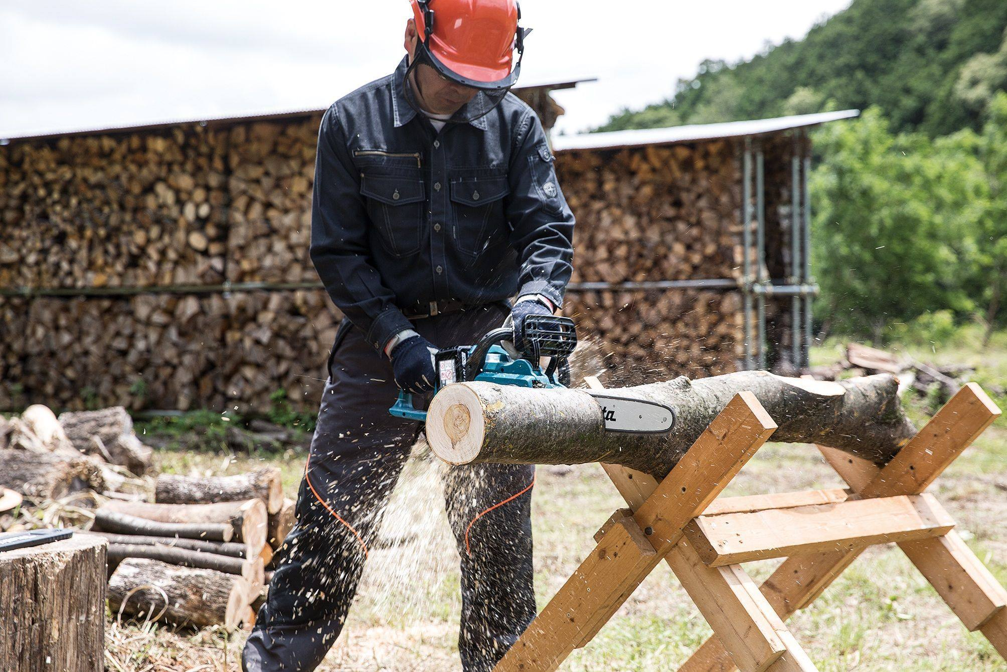 Chainsaw worker cutting logs
