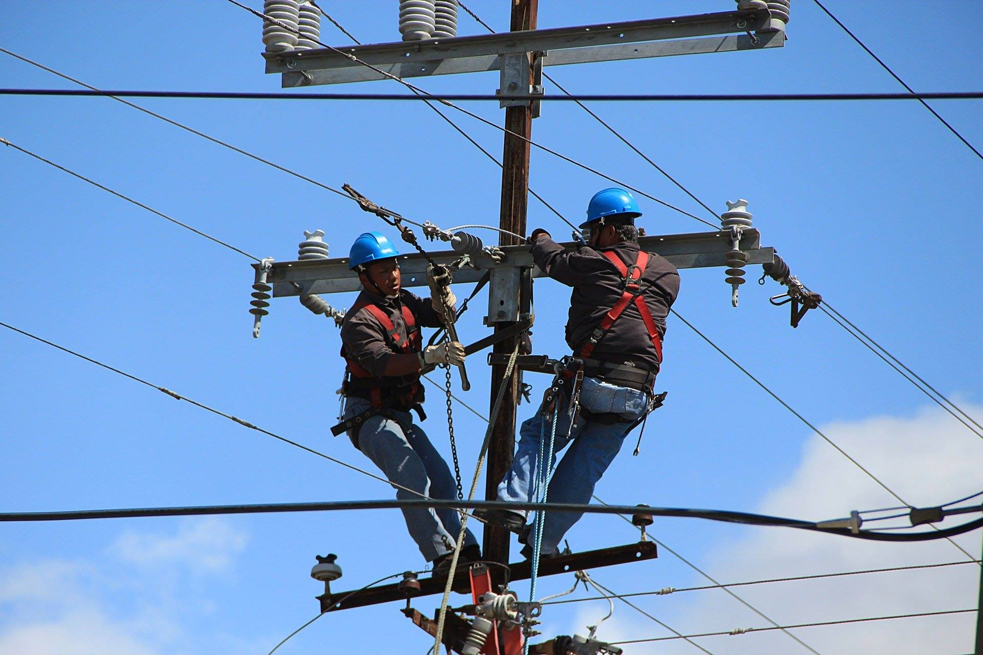 Two electrical workers on a pole