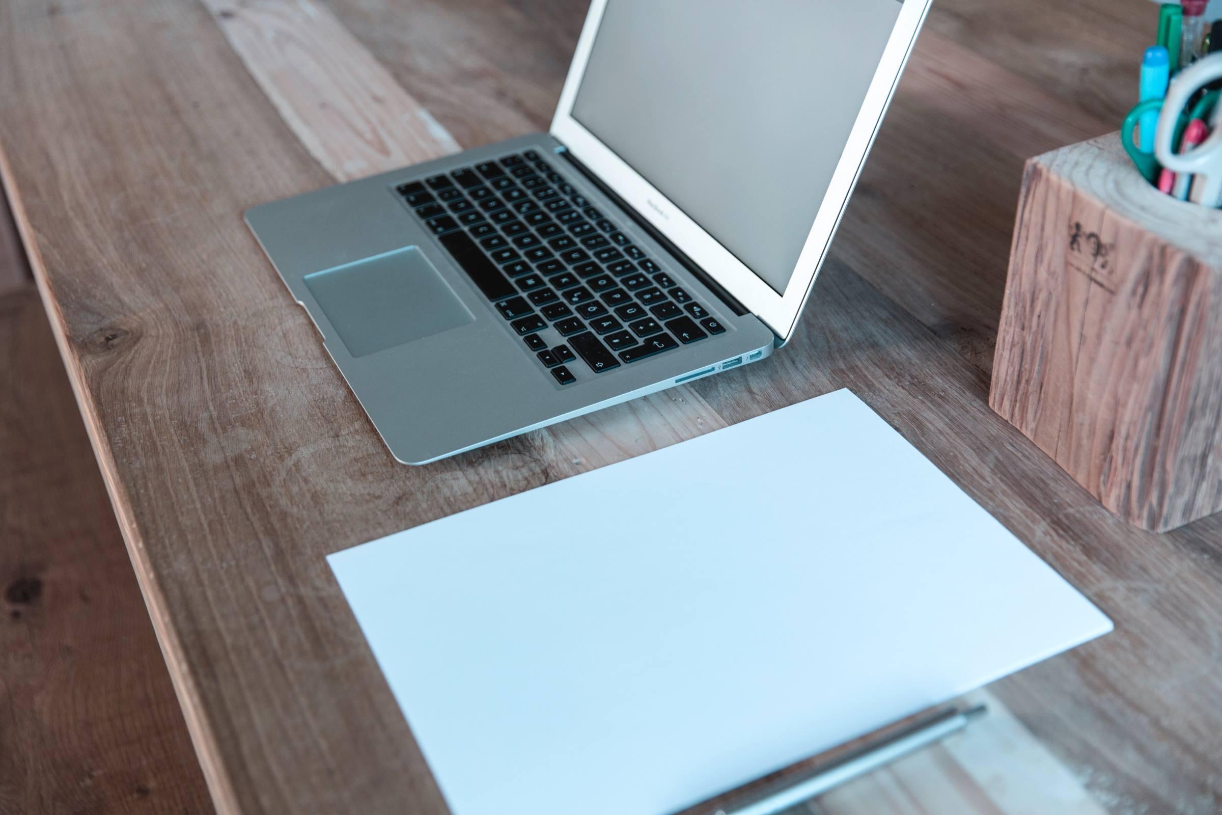 laptop pen paper desk office