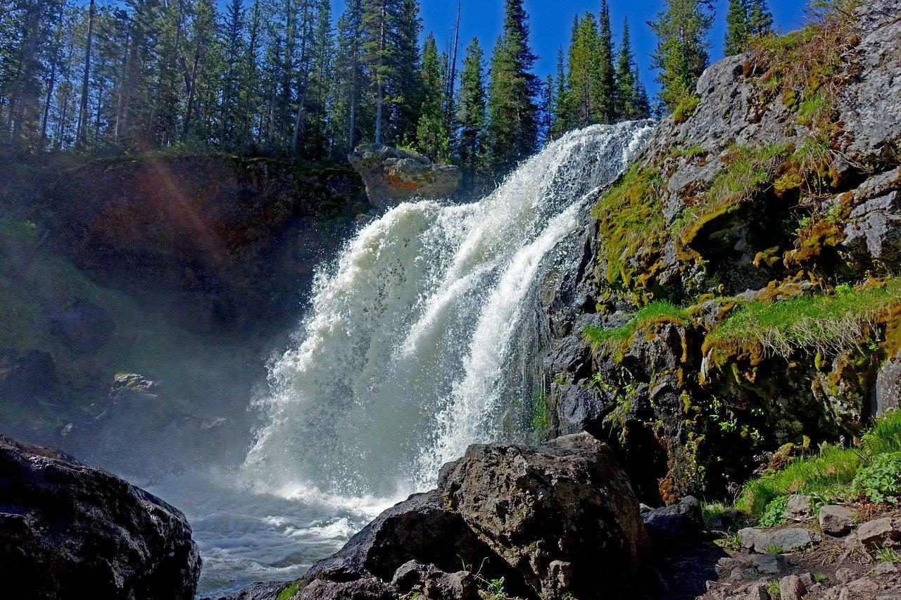 yellowstone national park waterfall trees blue sky