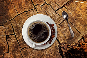 Cup of black coffee on tree stump