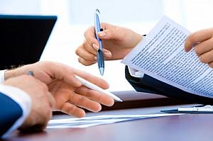 office papers pens people desk laptop
